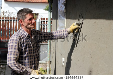 Construction Worker at work. Mason worker plastering wall. - stock photo