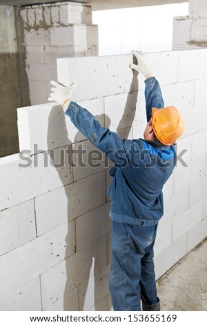 construction worker bricklayer builder installing lime sand brick during indoor wall creation - stock photo