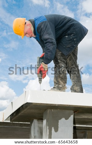 construction worker builder drilling a hole during roofing iron mounting at plate roof works