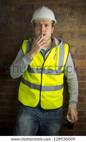 construction worker / builder on coffee / cigarette break leaning against brick wall