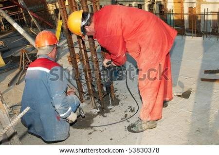 construction worker builders drilling a hole during assembling formwork for concrete filling - stock photo