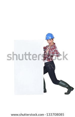 Construction worker by a billboard. - stock photo