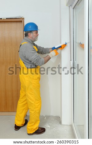 Construction worker caulking door or window with silicone glue using cartridge - stock photo