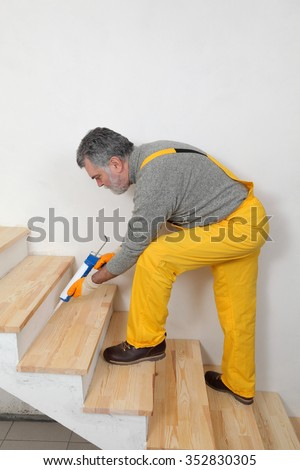 Construction worker caulking wooden stairs with silicone glue using cartridge