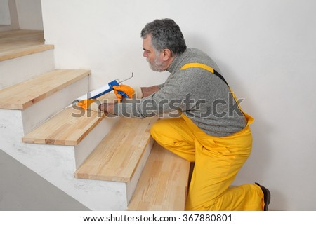 Construction worker caulking wooden stairs with silicone glue using cartridge, home renovation