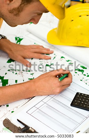 construction worker checking documents and maps - stock photo