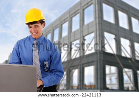 Construction Worker Checking Laptop in front of a Commercial Construction Building - stock photo