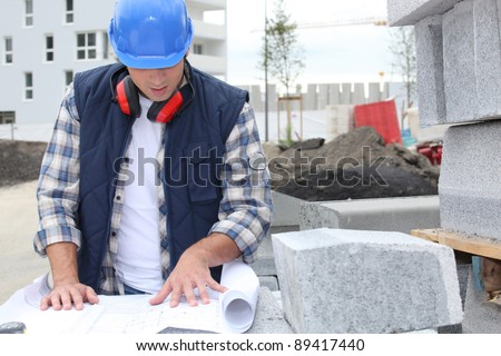 Construction worker checking plans - stock photo