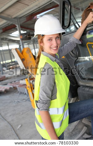Construction worker climbing on machine - stock photo