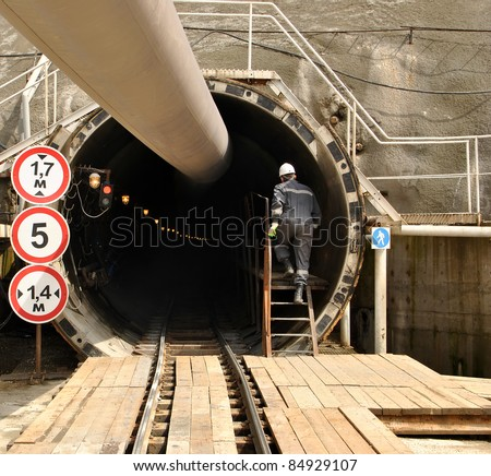 Construction worker climbs the stairs in the tunnel under construction. Technology adit tunnel complex combined rail and road to Krasnaya Polyana. - stock photo