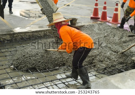 Construction Worker concrete surface on new sidewalk - stock photo