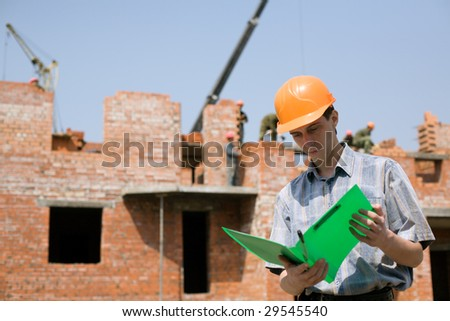 Construction worker.Construction of the house from a brick. - stock photo