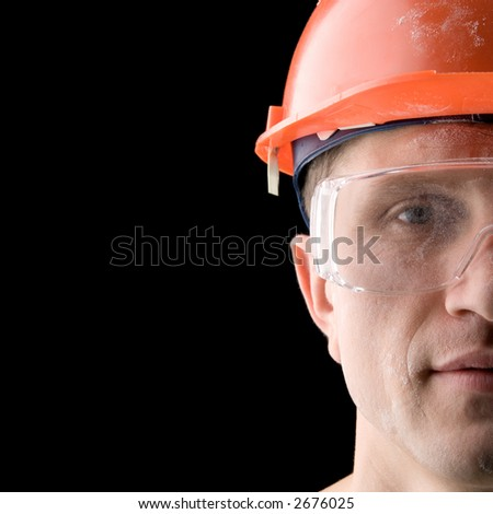 Construction worker covered with dust, isolated on black - stock photo