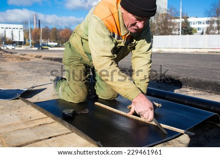Construction worker cutting roll roofing felt during waterproofing works - stock photo
