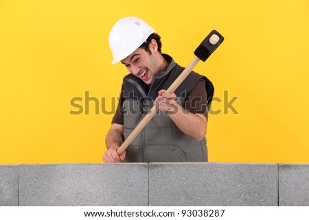 Construction worker destroying his work. - stock photo