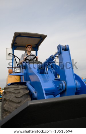 construction worker driving a bulldozer on a building site - stock photo
