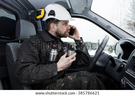 Construction worker driving a car, talking on the phone while drinking coffee in Finland. He is wearing a white helmet and he has a dirty overalls.  - stock photo
