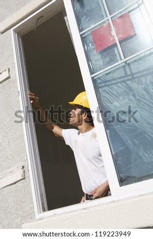 Construction Worker examining window frame - stock photo