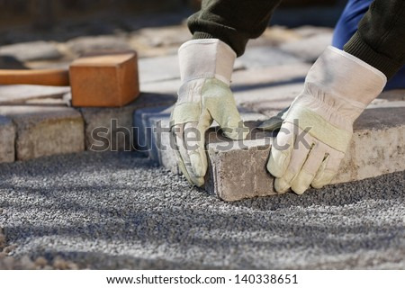 Construction worker fixing the pavestone on the road - stock photo