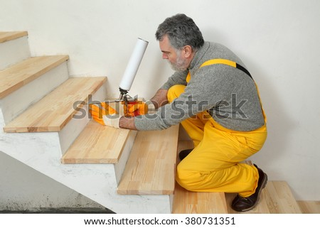 Construction worker fixing wooden stairs with polyurethane spray gun, home renovation