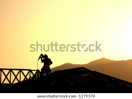 Construction worker framing a new home silhouetted against the evening sunset and mountains. - stock photo