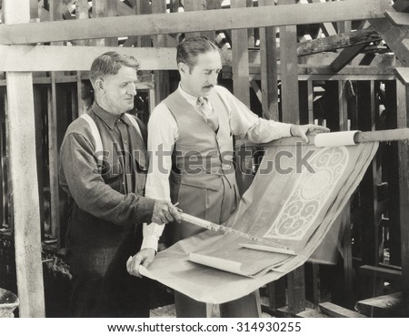 Construction worker going over plans with architect - stock photo