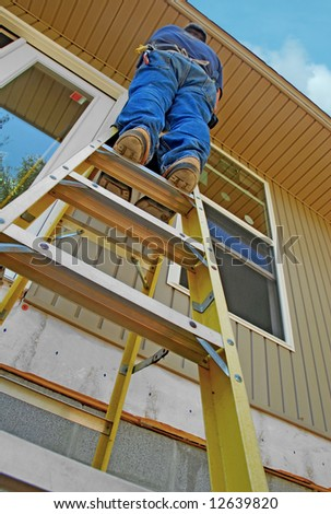 Construction worker high up on ladder - stock photo