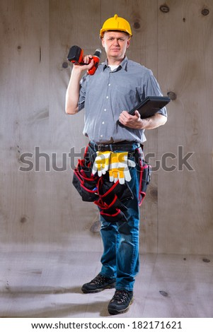 Construction worker holding a drill and a laptop - stock photo