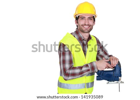 Construction worker holding a jigsaw - stock photo