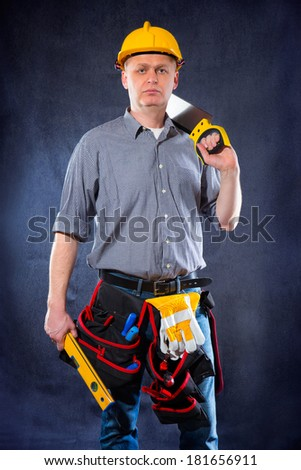 Construction worker holding a spirit level and saw - stock photo