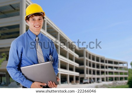 Construction Worker Holding Laptop in front of a Commercial Construction Building - stock photo