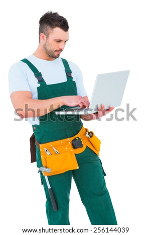 Construction worker holding laptop on white background - stock photo
