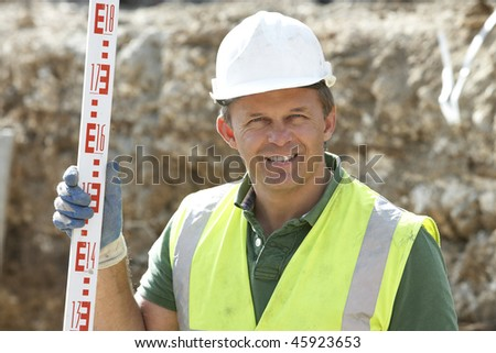 Construction Worker Holding Measure - stock photo