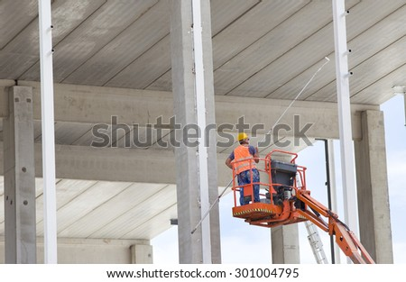 Construction worker holding rod with paint roller and standing in lifted cage for safety working on height at building site - stock photo