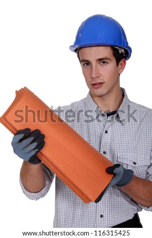 Construction worker holding roof shingles - stock photo