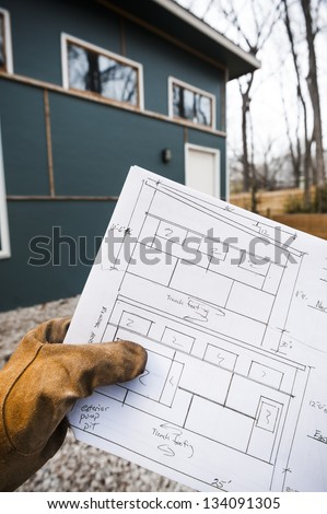 construction worker holding the blue prints for the building in the background