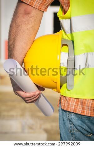 Construction worker holding yellow hardhat - stock photo