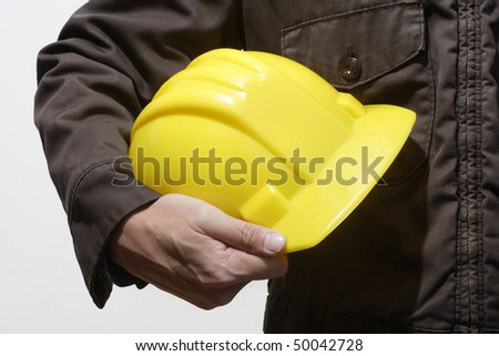 construction worker holding yellow hardhat on white background - stock photo