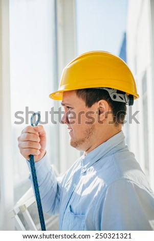 Construction worker holds a rope and a carbine. Full length studio shot .