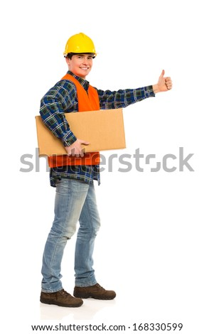 Construction worker holds carton box and showing thumb up. Full length studio shot isolated on white.