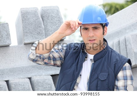 Construction worker in a hardhat next to concrete kerbing - stock photo