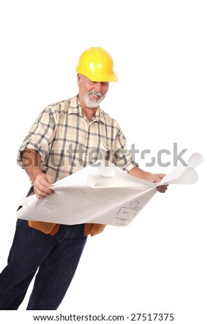 Construction worker in a tool belt and hardhat analyzing blueprints - stock photo