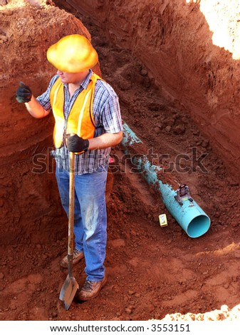 construction worker in a trench with a pipe
