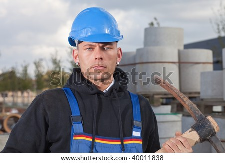 Construction worker in blue hard hat standing outdoors at construction site