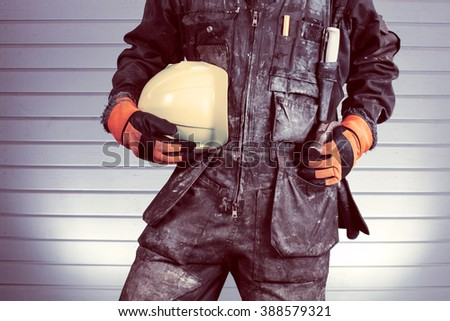 Construction worker in dirty overalls in Finland. The laborer have orange gloves, yellow helmet and hammer. Background out of focus and illuminated with flash. Image includes a vintage effect.