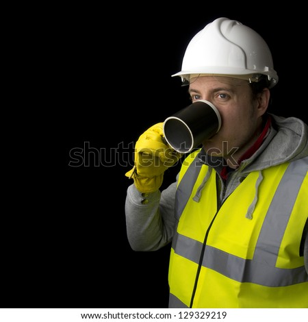 construction worker in helmet, high visability vest and gloves, taking a break from work, having a drink from a mug - stock photo