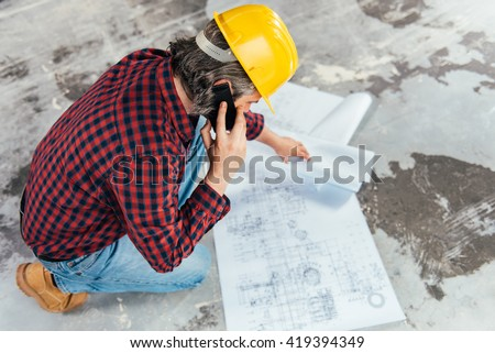 Construction Worker In Safety Helmet reading blueprints and talking on smart phone - stock photo