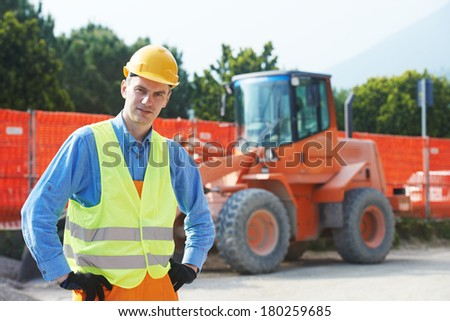 construction worker in safety protective work wear at construction site in front of loader machinery - stock photo