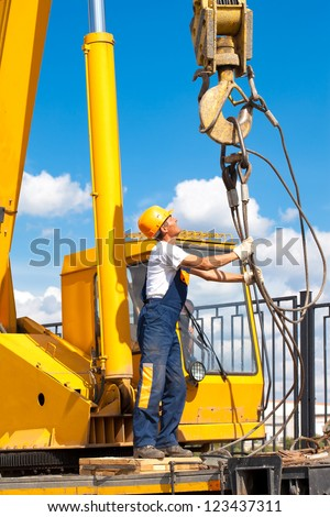Construction worker in uniform and protective gear during hoisting works by mobile crane - stock photo