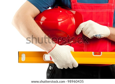 Construction worker in uniform holding hardhat and level isolated on white